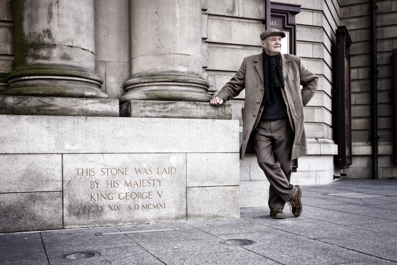 Stuart leans against the Usher Hall foundation stone laid by King George V and his Queen